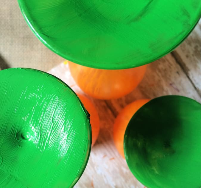 Paint green the stems of the large wine glass centerpieces for a fall decor idea