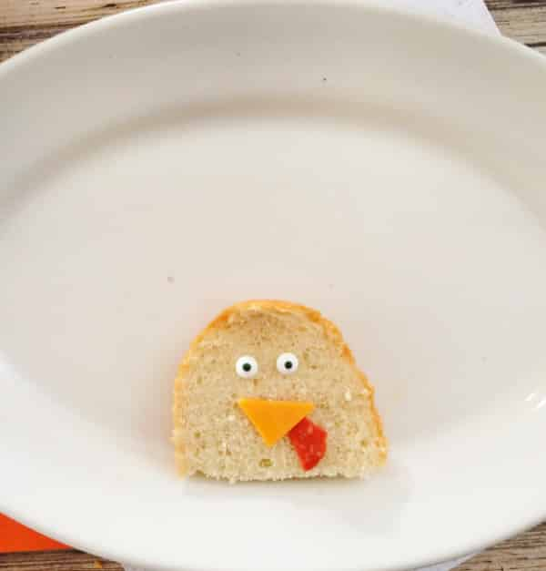 Start your meat and cheese turkey platter by crafting the turkey's 'head' using a piece of French bread
